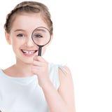 Retrato del primer de la niña que mira con magnificar Fotos de archivo