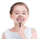 Retrato del primer de la niña que muestra los dientes con un magnificar Foto de archivo libre de regalías