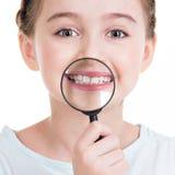 Retrato del primer de la niña que muestra los dientes con un magnificar Fotografía de archivo