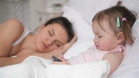 Retrato del primer de la niña y de la madre cansada en el dormitorio La mujer está durmiendo, su hija lista está utilizando a mad metrajes