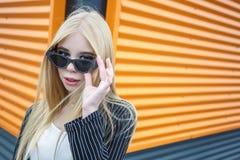 Retrato del primer de la pequeña muchacha modelo sonriente linda en chaqueta rayada y las gafas de sol que presentan cerca de na foto de archivo libre de regalías