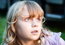 Retrato del primer de la pequeña muchacha rubia que mira para arriba Imágenes de archivo libres de regalías