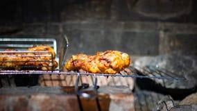 Retrato del primer de la pierna de pollo asada a la parrilla en parrilla natural del carbón imagenes de archivo