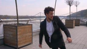 Retrato del primer de la sonrisa del baile y del salto del hombre de negocios que camina afroamericano atractivo joven feliz en almacen de video