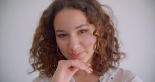 Retrato del primer de la sonrisa femenina del caucásico rizado de pelo largo bonito joven feliz presentando delante de la cámara  almacen de video