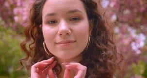 Retrato del primer de la sonrisa femenina del caucásico rizado de pelo largo joven en cámara alegre de mirada que se coloca al ai almacen de metraje de vídeo
