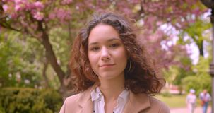 Retrato del primer de la sonrisa femenina del caucásico rizado de pelo largo joven en cámara feliz de mirada que se coloca al air almacen de video
