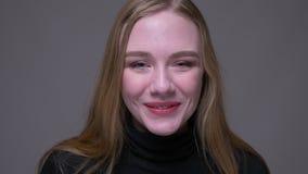 Retrato del primer de la sonrisa femenina morena atractiva joven en c?mara alegre de mirada con el fondo aislado encendido metrajes