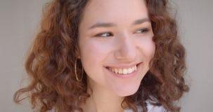 Retrato del primer de la sonrisa modelo femenina del caucásico rizado de pelo largo atractivo joven en cámara feliz de mirada con metrajes