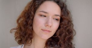 Retrato del primer de la sonrisa modelo femenina del caucásico rizado de pelo largo joven en cámara alegre de mirada con el fondo almacen de video