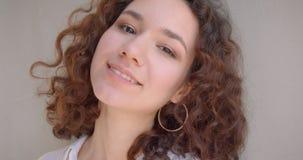 Retrato del primer de la sonrisa modelo femenina del caucásico rizado de pelo largo joven en cámara feliz de mirada con el fondo almacen de metraje de vídeo