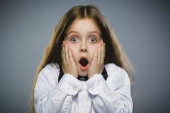 Retrato del primer de la sorpresa que va de la muchacha que se pregunta en fondo gris Imagen de archivo libre de regalías