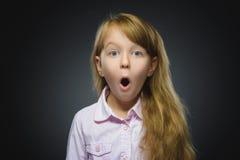 Retrato del primer de la sorpresa que va de la muchacha que se pregunta en fondo gris Imagenes de archivo