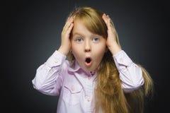 Retrato del primer de la sorpresa que va de la muchacha que se pregunta en fondo gris Foto de archivo