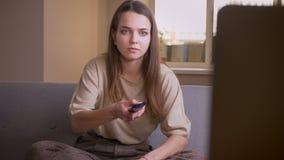 Retrato del primer de la TV de observaci?n femenina cauc?sica atractiva joven que se sienta en el sof? dentro en el apartamento almacen de video