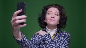 Retrato del primer de la vieja hembra morena caucásica que toma selfies en el teléfono con el fondo aislado en verde metrajes