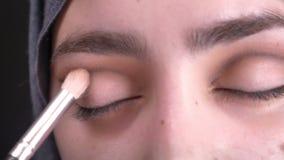 Retrato del primer de las manos femeninas que hacen el stumping del maquillaje del ojo con el cepillo para la mujer musulmán atra almacen de metraje de vídeo