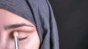 Retrato del primer de las manos femeninas que hacen el stumping del maquillaje del ojo con el cepillo para la mujer musulmán herm almacen de video