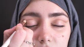 Retrato del primer de las manos femeninas que hacen maquillaje del ojo con el lápiz y el cepillo marrones para la mujer musulmán  almacen de metraje de vídeo