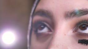 Retrato del primer de las manos femeninas que hacen maquillaje usando el rimel para la mujer musulmán hermosa en hijab en luces b almacen de metraje de vídeo