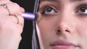 Retrato del primer de las manos femeninas que hacen maquillaje y que ponen la fundación para la mujer musulmán hermosa en hijab e almacen de video