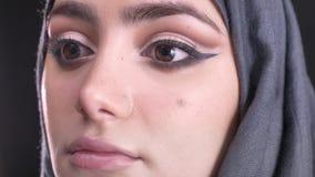 Retrato del primer de las manos femeninas que hacen maquillaje y que ponen la fundación para la mujer musulmán joven en hijab en  almacen de video