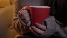 Retrato del primer de las manos femeninas que sostienen la taza roja con la bebida caliente en fondo casero acogedor almacen de video