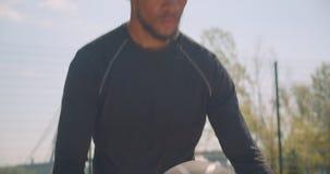 Retrato del primer de las manos masculinas afroamericanas deportivas que entrenan con una bola del baloncesto que calienta en la  almacen de metraje de vídeo