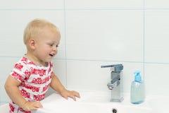 Retrato del primer de las manos que se lavan de un año del niño caucásico blanco lindo del muchacho en cuarto de baño y la mirada Imagen de archivo libre de regalías