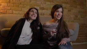 Retrato del primer de las muchachas caucásicas jovenes que ven la TV alegre y que beben el vino en fondo casero acogedor metrajes