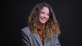 Retrato del primer de ligar sonriente femenino joven atractivo y de jugar con su pelo rizado marrón que mira derecho almacen de metraje de vídeo