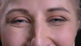 Retrato del primer de los ojos grises femeninos de mediana edad hermosos que miran la cámara con la expresión facial sonriente almacen de metraje de vídeo