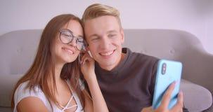 Retrato del primer de los pares caucásicos lindos jovenes que toman selfies divertidos en el teléfono dentro en el apartamento almacen de metraje de vídeo