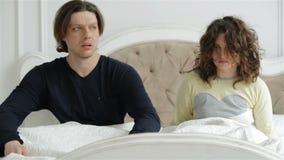 Retrato del primer de los pares confusos jovenes que durmieron más de la cuenta La mujer y el hombre en pijamas están despertando almacen de video