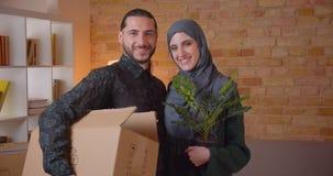 Retrato del primer de los pares musulmanes alegres jovenes que miran la cámara que se coloca en un apartamento nuevamente comprad metrajes
