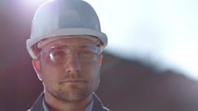 Retrato del primer de los vidrios que llevan masculinos y del casco del trabajador industrial que miran la c?mara almacen de video
