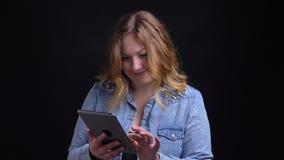 Retrato del primer de mandar un SMS femenino caucásico adulto en la tableta que mira la cámara y que sonríe con el fondo aislado almacen de video