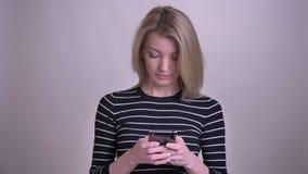 Retrato del primer de mandar un SMS femenino del caucásico rubio atractivo adulto en el teléfono y de la sonrisa con el fondo ais metrajes