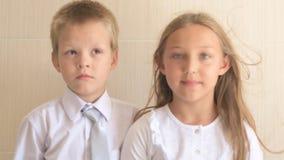 Retrato del primer de niños felices con los ojos azules y el pelo rubio en uniforme escolar Preescolares del muchacho y de la muc metrajes