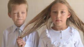 Retrato del primer de niños felices con los ojos azules y el pelo rubio en uniforme escolar Preescolares del muchacho y de la muc almacen de video