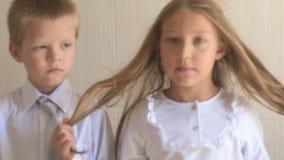 Retrato del primer de niños felices con los ojos azules y el pelo rubio en uniforme escolar Preescolares del muchacho y de la muc almacen de metraje de vídeo