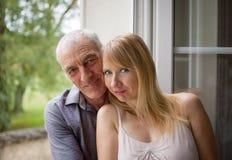 Retrato del primer de pares felices con la diferencia de la edad que abraza cerca de la ventana en su hogar durante día caliente  imagen de archivo