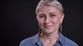 Retrato del primer de reír nerviosamente sonriente femenino del caucásico adulto rubio feliz y de mirar derecho la cámara almacen de metraje de vídeo