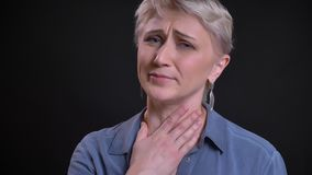Retrato del primer de toser femenino caucásico adulto enfermo teniendo una garganta enferma y mirando la cámara almacen de video