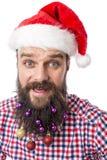 Retrato del primer de un hombre divertido con las bolas coloridas de la Navidad adentro Fotos de archivo