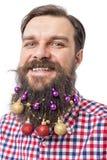 Retrato del primer de un hombre divertido con las bolas de la decoración en su bea Fotos de archivo libres de regalías
