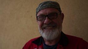 Retrato del primer de un hombre gris-barbudo sonriente con vidrios y una venda almacen de video