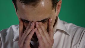 Retrato del primer de un hombre gritador Un hombre de negocios joven se cierra los ojos de dolor con los rasgones en fondo verde almacen de video