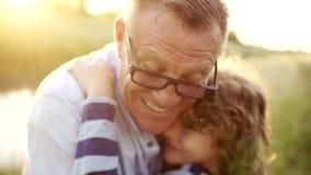 Retrato del primer de un hombre maduro que abraza a su último hijo Paternidad feliz Niño rizado, hombre que lleva los vidrios ópt almacen de video