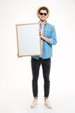 Retrato del primer de un hombre sonriente que lleva a cabo al tablero en blanco Imagen de archivo